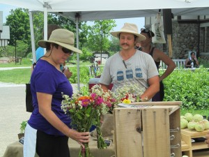 Kyle from Harvest Moon Farm showing fresh cut flowers to a visitor at Duke Farms' Farm To Table farmers market.